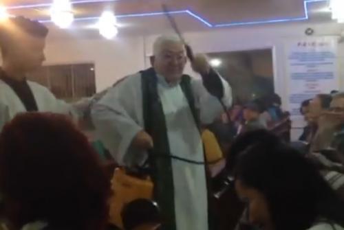 Padre abençoa fiéis em missa usando pulverizador costal manual